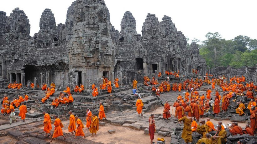 Cambodian Buddhist monks sit at Bayon te